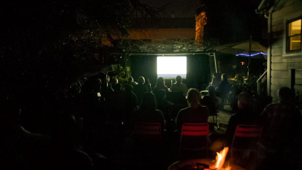 Guests watch the film outside in the garden at Backwater Arts in San Jose